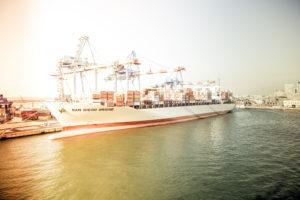 Containerskip i havn blir lastet/losset